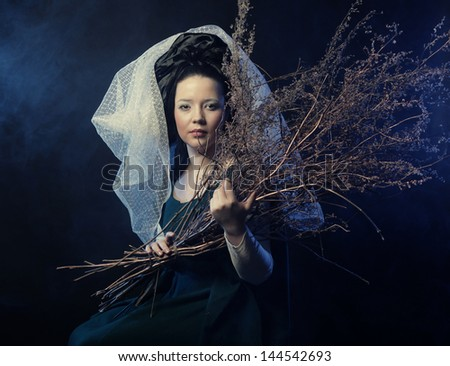 girl in medieval dress  with bunch of sticks in smoke - stock photo