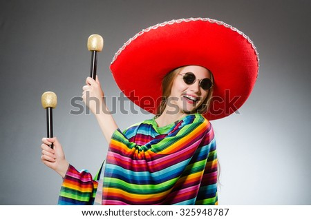Girl in mexican vivid poncho with maracas against gray - stock photo