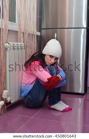 Girl in mittens and hats bask near radiator - stock photo