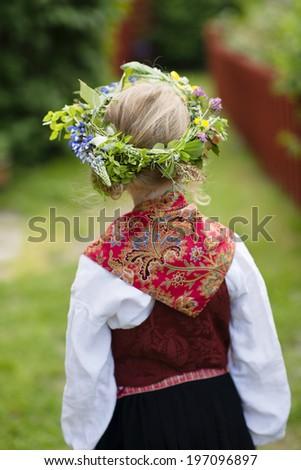 Girl in national costume wearing flower wreath, Sandhamn, Sweden - stock photo