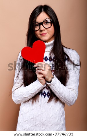 Girl in nerd glasses with red heart - stock photo