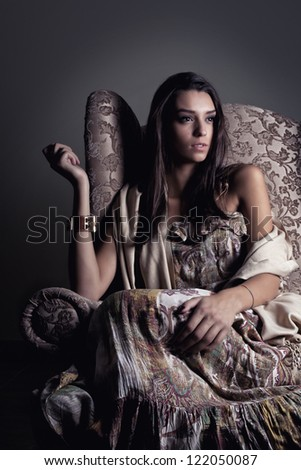 Girl in old armchair thinking - stock photo
