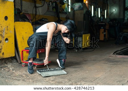 Girl in overalls in the garage puts or takes the instrument out of the case - stock photo