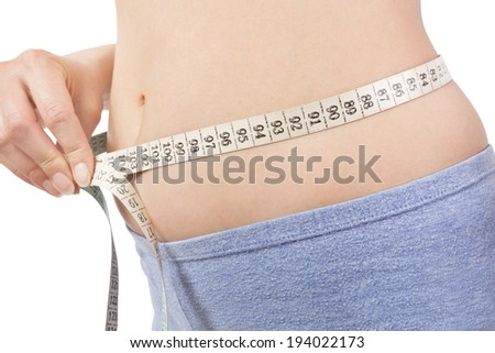 Girl in panties measuring her body with tape measure detail isolated on white. Belly detail. Weight loss and diet. - stock photo