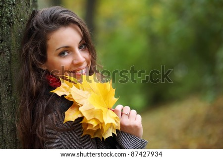 Girl in park colourful autumn. Holding vivid bouquet of foliage in hands - stock photo