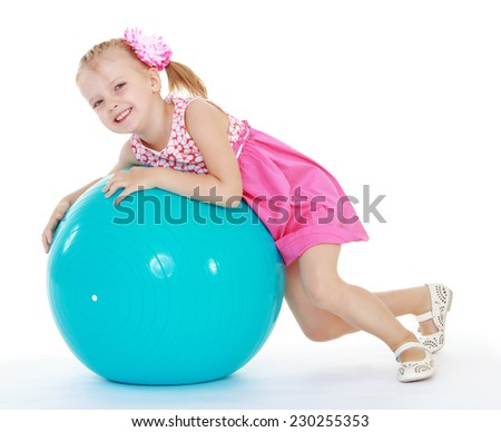 Girl in pink dress lies on a large exercise ball.Very cheerful little girl. - stock photo