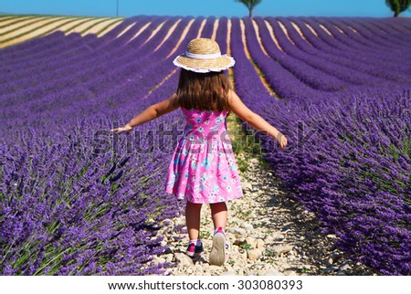 Girl in pink dress walking in lavender field - stock photo
