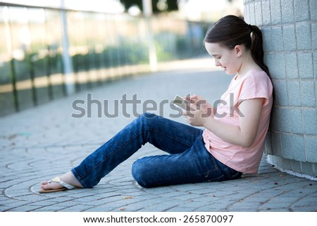 Girl in pink shirt oudoors looking at her tablet computer or technology device communicating - stock photo