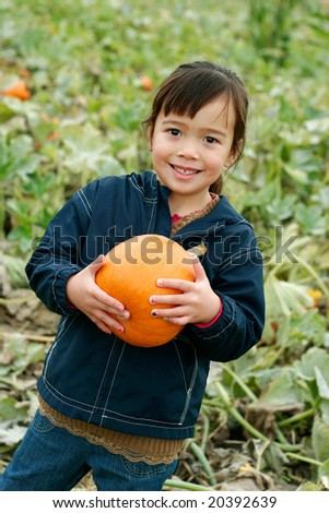 Girl in Pumpkin Patch holding a Pumpkin - stock photo