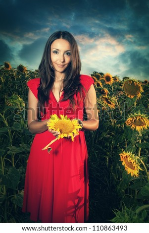 Girl in red dress at sunflowers field - stock photo