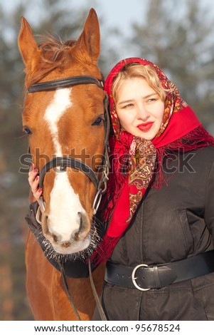 Girl in red headscarf and Russian Don horse at winter day - stock photo