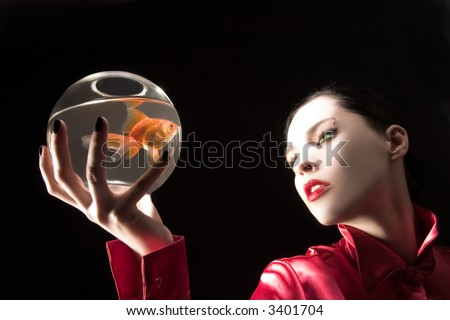 girl in red with goldfish on glass tank - stock photo