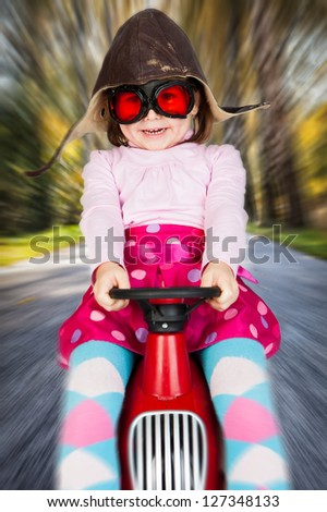 Girl in retro racing hat and goggles driving on toy car at speed with blurred background. - stock photo