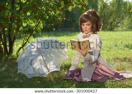 Girl in retro style dress reads book in the park with sun umbrella beside her                     - stock photo