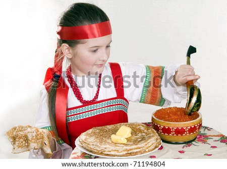 girl in Russian national clothes behind a table with pancakes and red caviar. A Shrovetide. - stock photo