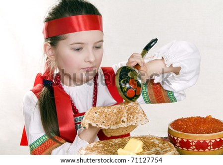 girl in Russian national suit behind a table imposes a wooden spoon red caviar on a pancake. A pancake week. - stock photo