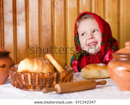 Girl in Russian shawl with rolls and honey - stock photo
