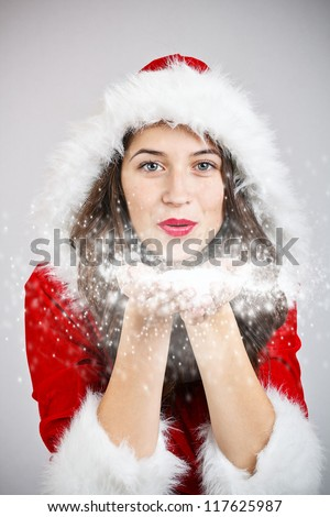 Girl in santa cloth blowing snow from hands - stock photo
