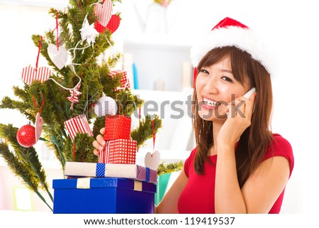 Girl in santa hat call mobile phone beside christmas tree. Indoor / inside house - stock photo