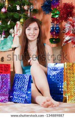 Girl in Santa hat sits with christmas gifts - stock photo