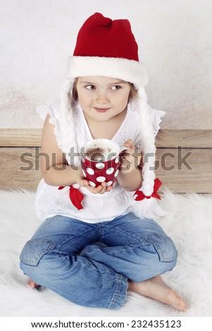 Girl in Santa's hat drinking cocoa - stock photo