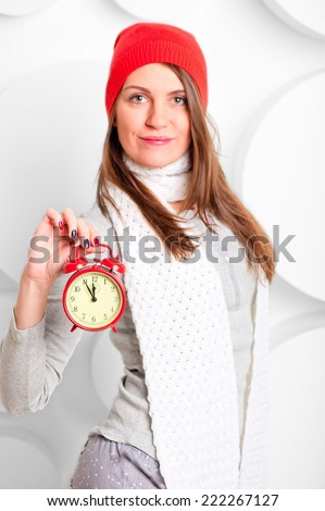 girl in scarf and hat shows the time on the alarm clock  - stock photo