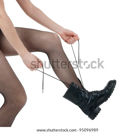 Girl in sexy pantyhose lacing her army-style black boots. - stock photo