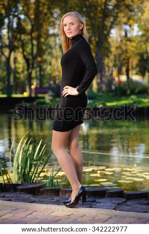 Girl in short black dress against the pond in the city-park - stock photo