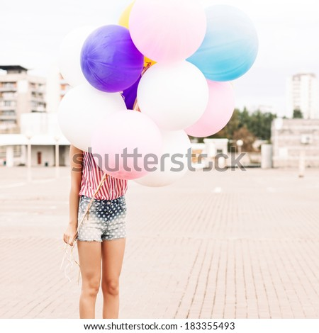 girl in short jeans shorts, sleeveless striped top and high heels stands in bunch of balloons - stock photo