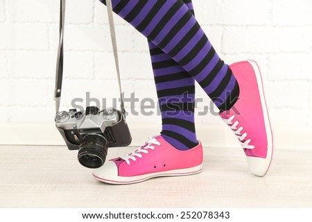 Girl in sneakers with retro photo camera in room - stock photo
