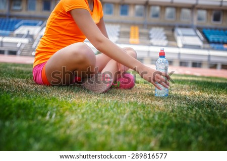 Girl in sportswear with bottle of water sitting on stadium grass. - stock photo