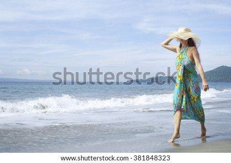 Girl in summer dress and hat, standing on the shore and watch the sea - stock photo