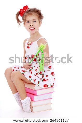 Girl in summer dress sitting on a stack of books  - isolated on white background - stock photo