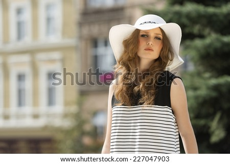 Girl in summer hat on the street. She is looking at camera and she wears striped dress and nice makeup. - stock photo
