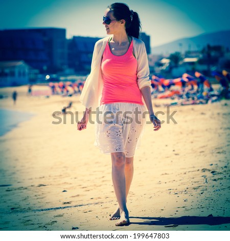girl in sunglasses in white skirt on the beach - stock photo