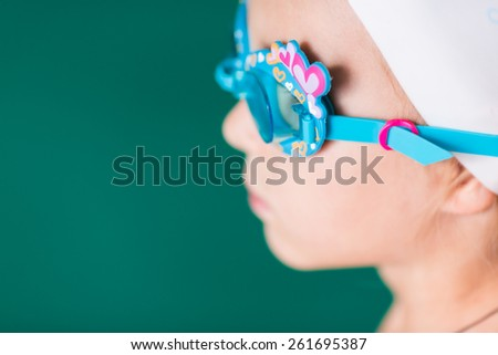 Girl in swimming glasses in swimming pool training - stock photo