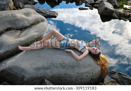Girl in swimwear and shorts lying on the stone at the water - stock photo