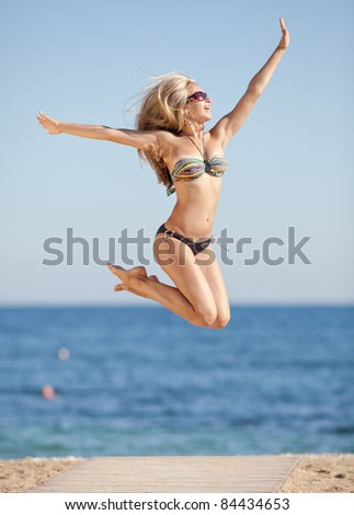 Girl in swimwear at the sea. Attractive young woman jumping outdoors. - stock photo