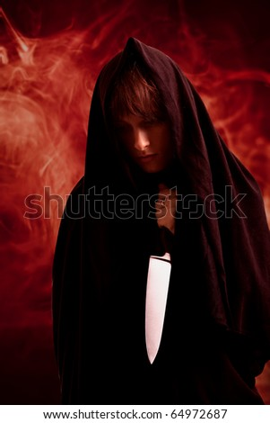 Girl in the black sheet with the knife - stock photo
