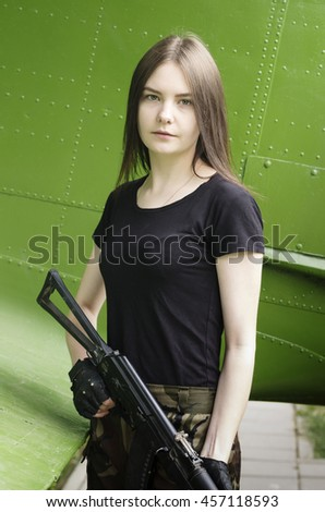Girl in the black T-shirt with a gun, posing near the fuselage military transport aircraft - stock photo