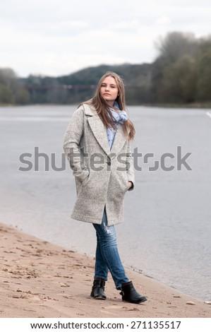 Girl in the coat posing near the river - stock photo