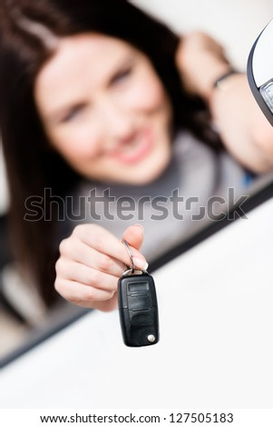 Girl in the convertible car shows car key. Buying car and getting the freedom - stock photo