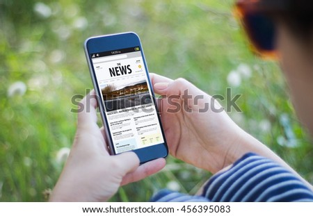 girl in the grass holding her smartphone and reading news. All screen graphics are made up. - stock photo