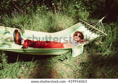Girl in the hammock. Little curly girl in sunglasses in hammock on nature. Adorable girl in hammock outdoor at holidays vacation. Child on holidays outdoors at summer. - stock photo