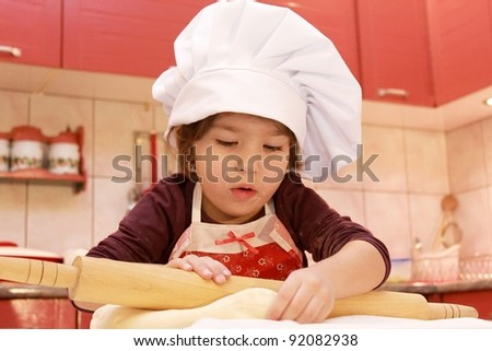 Girl in the kitchen with rolling pin - stock photo