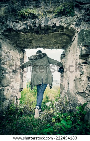 Girl in the old castle tunnel - stock photo