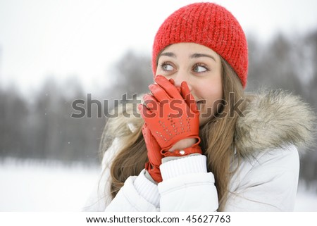 Girl in the Park laughs, closes his hand in mittened red - stock photo