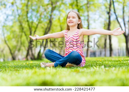 Girl in the park sitting on the grass and spread her arms - stock photo