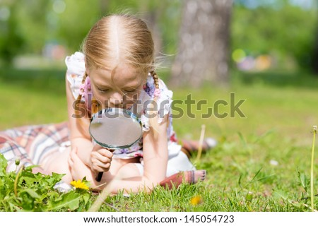 girl in the park with a magnifying glass considers plants - stock photo