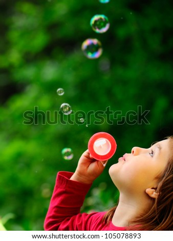 Girl in the park with bubbles. - stock photo